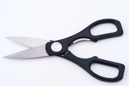 sharpened: Scissors are hand-operated shearing instruments. They consist of a pair of metal blades pivoted so that the sharpened edges slide against each other when the handles (bows) opposite to the pivot are closed. Stock Photo