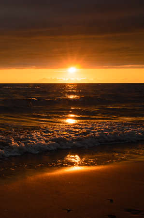 Bright sunset after the storm in the Baltic sea in summer. Sun shine above horizon.
