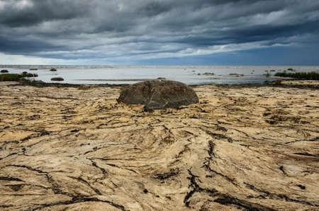 Dry crannied ground and cloudy sky on the beach. Big stone in the center. Baltic Sea coastline, Estonia.