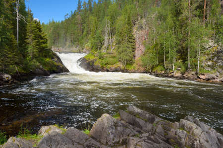 View from the river bank on waterfall in northern Finland in summer.