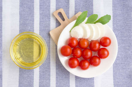 Flat lay with cherry tomatoes, cheese and vegetable oil. Still life on a kitchen towel.