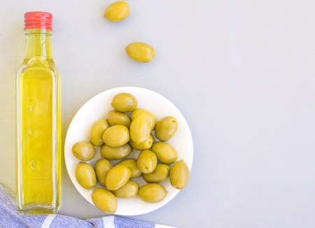 A glass bottle of olive oil, a bowl of olives, and a towel. Grey background, space for text