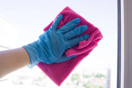 Washing windows. A blue-gloved hand holds a rag and wipes the glass Banque d'images