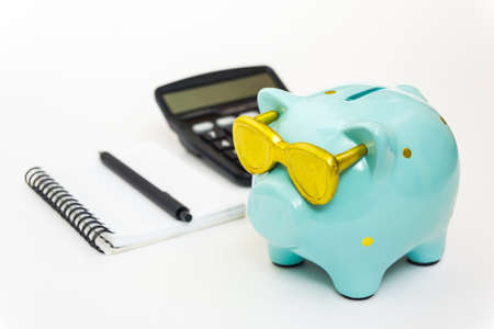Piggy Bank with glasses a green color with a Notepad and calculator. The concept of saving money, Finance, and budget planning. Banque d'images