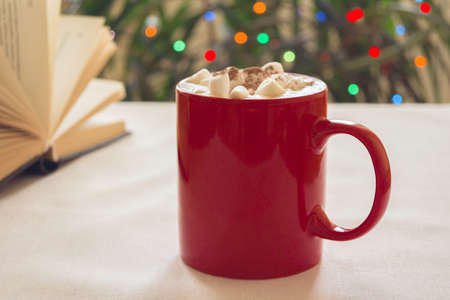 Red mug with coffee and marshmallows on the table. Next to a book and a background of lights. New year mood