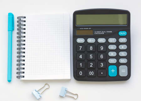 The calculator is on the table, next to an open empty notebook and a turquoise pen. Illustration of financial notes and mathematical calculations
