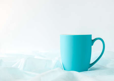 Blue mug on an airy fabric. Morning drink mood. Minimalistic design Banque d'images