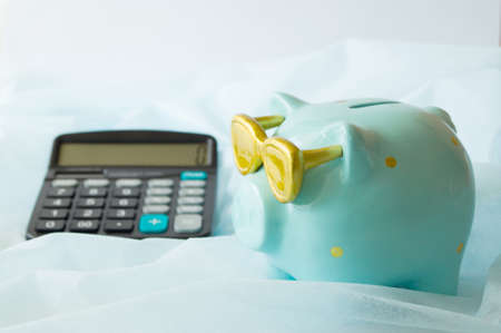 Piggy Bank aquamarine color and calculator. The concept of saving money and planning a financial budget