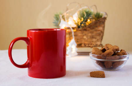 Red mug with coffee and cookies on the table. Next to the Christmas decoration and garland. New year mood
