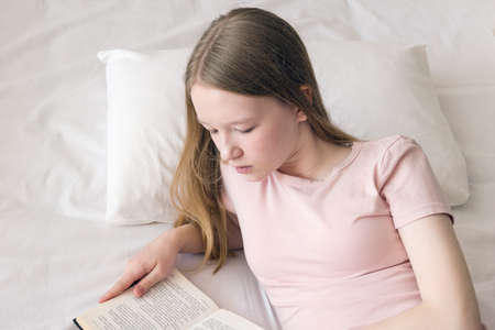 A young girl with long blonde hair is reading a book while lying on the bed