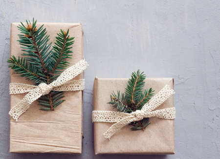 Flat lay with two new years gifts on a gray background. Simple paper packaging, spruce twigs. Banner with a Christmas theme, space for text Banque d'images