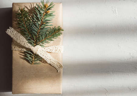 A rectangular box in a paper package is decorated with a spruce twig. Christmas gift in a minimalistic style on a cement background Banque d'images
