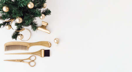Banner with hairdressing tools in gold color and a Christmas tree on a white background. Holiday template with hair salon accessories with space for text. Flat lay with Hairstylist's scissors. 版權商用圖片