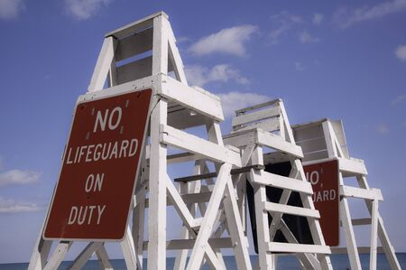 baywatch: Empty lifeguard tower chair with not on duty sign