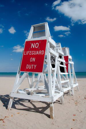 Empty lifeguard tower chair with not on duty sign photo