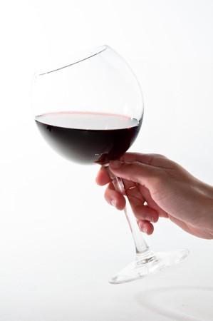 흰색 배경 위에 빨간색 와인 잔을 들고 여성 손 스톡 콘텐츠