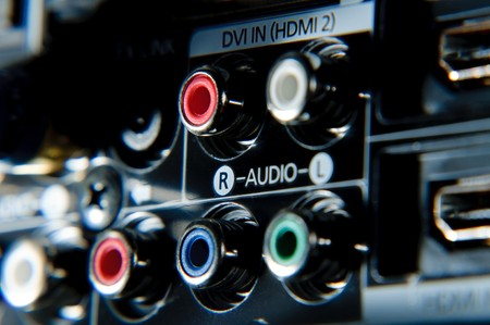 Red, white, green and blue rca connections behind high definition tv. Stock Photo