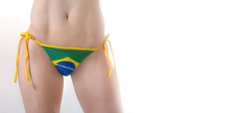 Beautiful Brazilian model wearing a green and yellow soccer thong bikini bottom isolated over white background Zdjęcie Seryjne