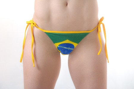 Beautiful Brazilian model wearing a green and yellow soccer thong bikini bottom isolated over white background Stock Photo