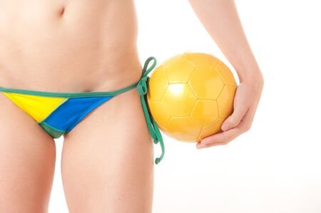 Beautiful Brazilian model wearing a green and yellow soccer thong bikini bottom  holding a soccer ball isolated over white background Stock Photo - 8264860
