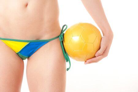 bikini bottom: Hermosa modelo brasile�a con un fondo de color verde y amarillo de f�tbol thong bikini sosteniendo una pelota de f�tbol aislada sobre fondo blanco
