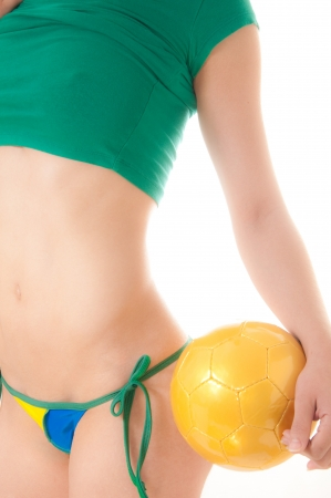 thongs: Beautiful Brazilian model wearing a green and yellow soccer thong bikini bottom  holding a soccer ball isolated over white background