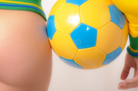 Beautiful Brazilian model wearing a green and yellow soccer thong bikini bottom  holding a soccer ball isolated over white background photo