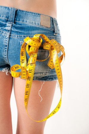 Model wearing blue jeans shorts holding a yellow measuring tape and red dumbells photo