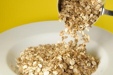 avena: Medici�n taza de cereal org�nico vertiendo en plato blanco sobre fondo amarillo multicolor