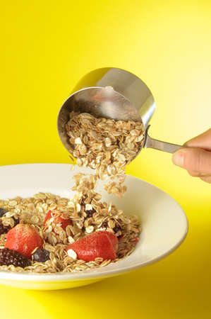Model using measuring cup to serve organic cereal on white plate over colorful yellow background photo