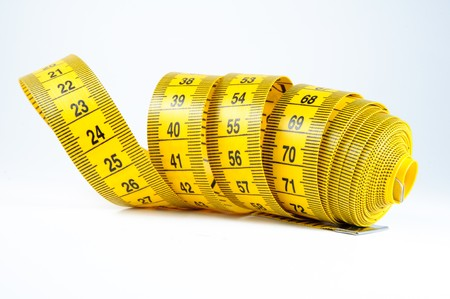Roll of yellow measuring tape rolled up over white background photo