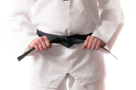 asian art: Man in martial arts uniform holding his black belt with both hands