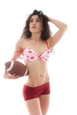 anniversary sexy: Beautiful woman holding a football wearing a pink hearts bra symbolizing Valentiness Day and American Football. Stock Photo