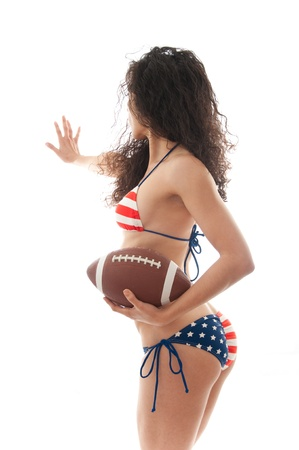 Beautiful woman wearing the United States flag bikini holding a football isolated over white background photo