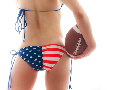 sexy bikini girl: Beautiful woman wearing the United States flag bikini holding a football isolated over white background
