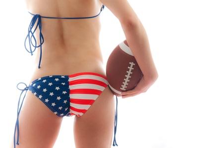 ni�as en bikini: Hermosa mujer llevando el bikini de bandera de Estados Unidos mantiene un f�tbol aislado sobre fondo blanco