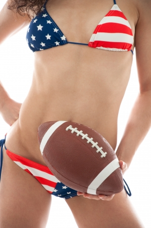 summer wear: Beautiful woman wearing the United States flag bikini holding a football isolated over white background