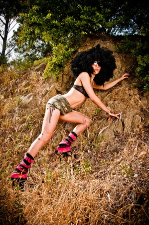 fro: Vintage seventies style model posing with a disco wig in nature Stock Photo