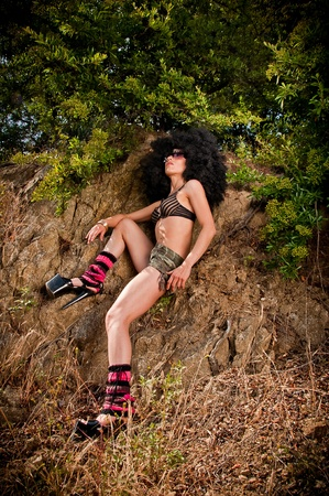 Vintage seventies style model posing with a disco wig in nature photo