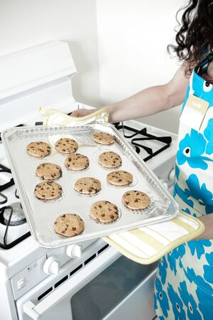 Beautiful woman baking cakes and cookies in a white home kitchen oven Stock Photo - 9943037