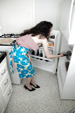 Beautiful woman baking cakes and cookies in a white home kitchen oven photo