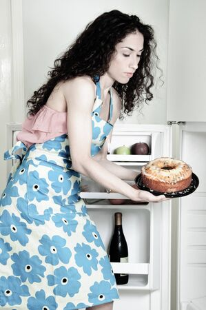 Beautiful woman baking cakes and cookies in a white home kitchen oven 스톡 콘텐츠