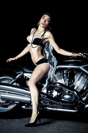 Beautiful biker model posing with motorcycle photo