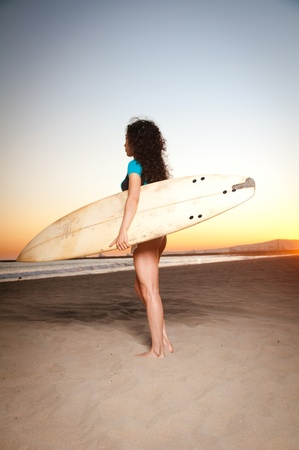 Beautiful model wearing a white bikini and surfer outft holding a surfboard during sunset by the beach photo