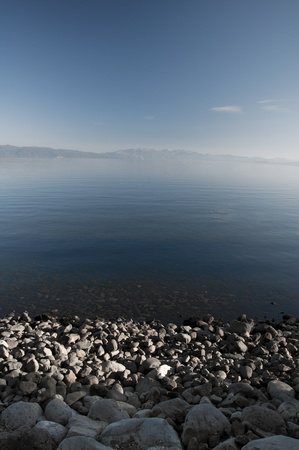 Rocky shore and mountain background at blue lake Stock Photo - 11262913