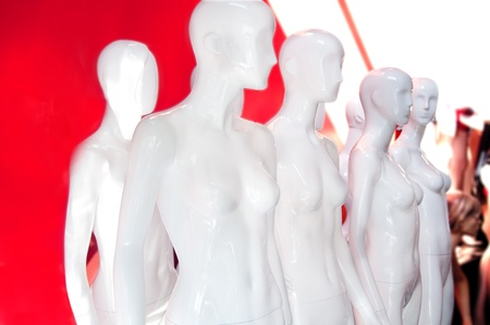 Eight white store fashion female mannequins displayed grouped together