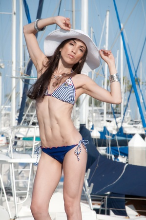 Sailor model wearing a blue nautical bikini in the marina by the ocean beach. photo