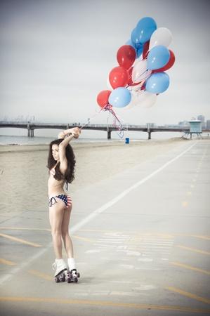 Beautiful model wearing the United States flag bikini on skates holding USA color ballons at the beach sidewalk Stock Photo - 13339825