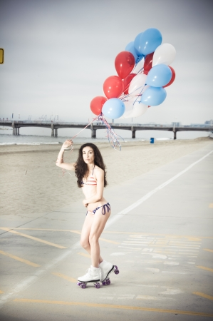 Beautiful model wearing the United States flag bikini on skates holding USA color ballons at the beach sidewalk
