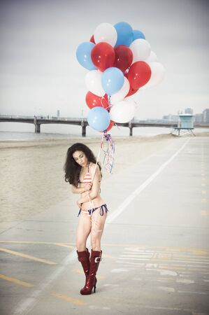 beach ball girl: Beautiful model wearing the United States flag bikini on skates holding USA color ballons at the beach sidewalk
